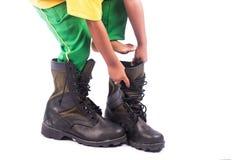 Tentativa do rapaz pequeno que veste a sapata grande imagem de stock