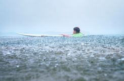 Tentativa do surfista da primeira etapa do rapaz pequeno a levantar-se a bordo sob o trop imagens de stock royalty free