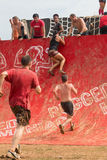Tentativa dos concorrentes de escalar a parede na raça extrema do curso de obstáculo Imagens de Stock