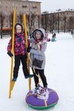 Tentativa feliz e satisfeita da mãe e da criança a andar em pernas de pau no inverno As atividades sociais realizam-se em feriado imagens de stock royalty free