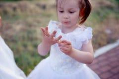 Tentativa pequena da menina para vestir as alianças de casamento imagem de stock