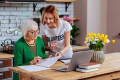 Tentativa voluntária persuadir a mulher idosa assinar o empréstimo expirado imagem de stock