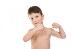 Tentativas do rapaz pequeno para mostrar seus músculos do bíceps Imagens de Stock