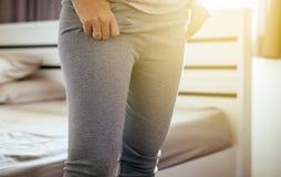 Tentative de femme la mettant ou portant pantalon dans le vestiaire photographie stock