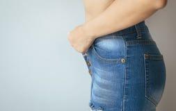 Tentative de femme la mettant ou portant pantalon dans le vestiaire image stock