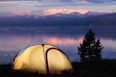 Tente à travers le beau coucher du soleil sur le lac Photo libre de droits