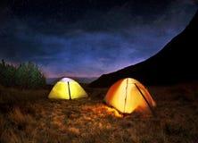 Tente de camping jaune lumineuse sous des étoiles Photos libres de droits