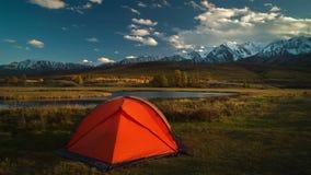Tente de touristes dans le camp parmi les prés alpins dans les montagnes au coucher du soleil clips vidéos