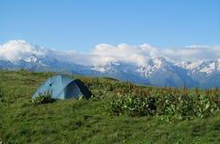 Tente de touristes sur l'herbe haute dans les montagnes avec de belles crêtes rocheuses couvertes de neige sur le fond Images stock