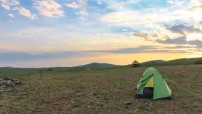 Tente de touristes sur le fond d'un coucher du soleil un jour chaud d'été dehors Photo libre de droits