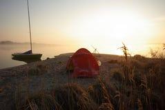 Tente et bateau à voile au lever de soleil Photographie stock libre de droits