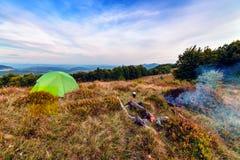 Tente et feu de camp en montagnes Image stock