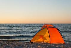 Tente lumineuse de jaune orange vide sur l'aube de bord de la mer Photo libre de droits