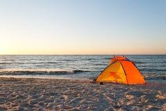 Tente lumineuse de jaune orange vide sur l'aube de bord de la mer Photo stock