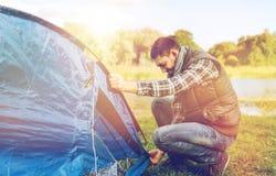 Tente masculine heureuse d'arrangement de voyageur dehors Images libres de droits