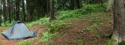 Tente nichée en terrain de camping de région sauvage de matin. Images stock