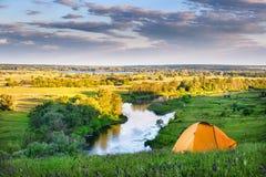 Tente orange sur la haute banque de la rivière Photographie stock
