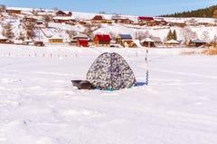 Tente pour la glace pêchant sur le fond d'un paysage rural d'hiver photo stock