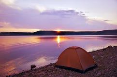 Tente près du lac au coucher du soleil Image libre de droits