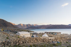 Tented tourist camp at Pangong Lake.Light and shade from sunrise. Pangong Tso, Tibetan for long, narrow, enchanted lake, also referred to as Pangong Lake, is an Royalty Free Stock Image