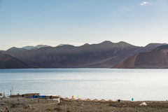 Tented tourist camp at Pangong Lake.Light and shade from sunrise. Pangong Tso, Tibetan for long, narrow, enchanted lake, also referred to as Pangong Lake, is an Stock Image