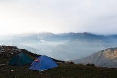 Tenten op de bovenkant van de berg in Himalayagebergte stock foto