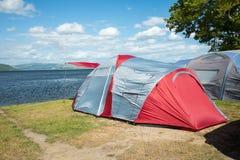 Tenten op een het kamperen plaats dichtbij een meer Royalty-vrije Stock Afbeeldingen