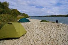 Tenten op het zandige strand op de rivier Stock Afbeeldingen