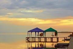 Tentes au-dessus de l'eau de mer au coucher du soleil Photographie stock
