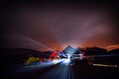 Tentes de camping lumineuses la nuit dans la zone d'alpin Image stock