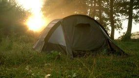 Tentes de touristes sur la rive au lever de soleil banque de vidéos