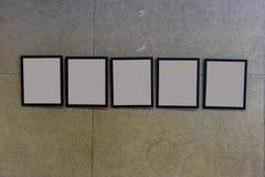tentoonstellingszaal met concrete muren en lege omlijstingen Stock Afbeeldingen