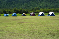 Tents. Camping in a campground with the green forest background Royalty Free Stock Photos