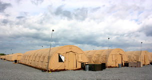 Tents. Camp with line of yellow tents  and light posts on a cloudy sky background Royalty Free Stock Image