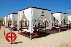 Tents on the beach. Leisure camp of white linen tents right on the sea shore Stock Photos