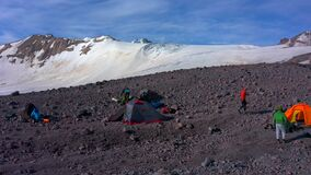 Tents camp in front of Mount Elbrus. Travelers collect their backpacks.