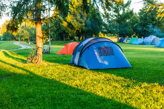 Tents Camping area in beautiful natural place. With trees and green grass stock image
