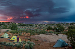Tents in desert with pink thunder storm sky. Three small tents in a desert landscape with a dramatic pink and blue thunderstorm sky and arches national park in royalty free stock photos