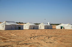 Tents in desert. Row of white camp tents in desert Stock Photos