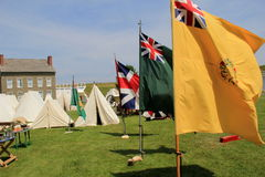 Tents and flags set up in front of stone buildings during reenactments, Fort Ontario, New York, 2016 Royalty Free Stock Photography