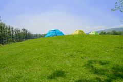 Tents on grassy hilltop in sunny summer afternoon. Tents on the grassy hilltop in sunny summer afternoon stock photography