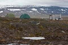 Tents and hut in tundra in the Svalbard Stock Images