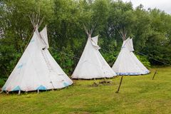 Tents of Indians. Standing in a meadow among trees stock image