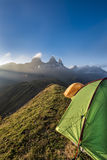 Tents on a mountain edge in front of the Aiguille d'Arves at sun Stock Images