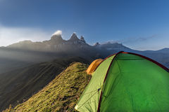 Tents on a mountain edge in front of the Aiguille d'Arves at sun Stock Photos