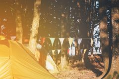 Tents pitched at a campsite amongst trees. With garlands of colorful festive bunting or flags strung between trunks with the sun glow in the left corner royalty free stock images