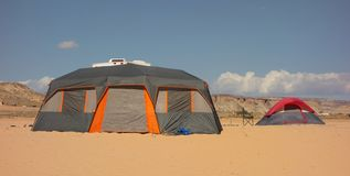 Tents pitched in the desert beside a reservoir in the summertime. Rustic camping as seen at popular lone rock, utah on memorial day weekend stock image