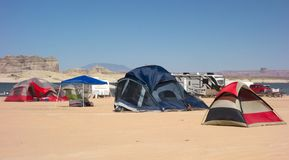 Tents pitched in the desert beside a reservoir in the summertime. Rustic camping as seen at popular lone rock, utah on memorial day weekend royalty free stock photos