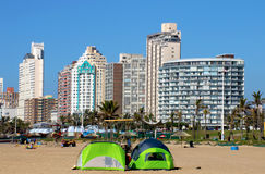 Tents Pitched 0n Beach Against City Skyline Stock Photography