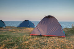 Wild camping tents near sea shore. Free camping with tents on coast Royalty Free Stock Photo
